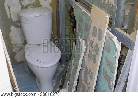 Ruined Toilet Lavatory Room During Renovation With Cleaned Walls From Tile And Gypsum Cardboard. Con