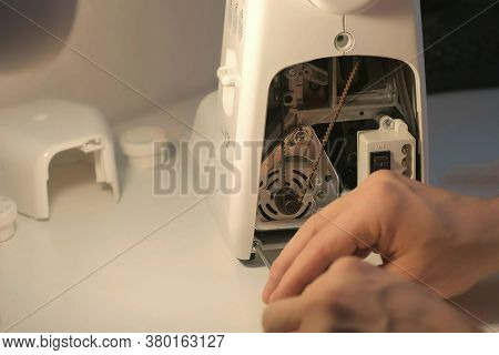 Repairman Master Is Collecting And Testing Sewing Machine After Repairing Sitting At Table In Worksh
