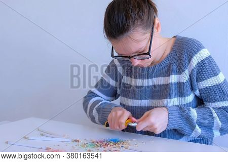 Young Woman Painter Artist In Glasses Sharpening Pencil Using Sharp Knife In Art Studio. Teacher Sha