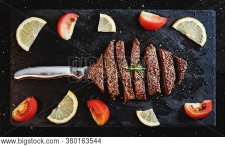 Grilled Beef Steak, Tenderloin On Black Stone Plate With Tomato And Lemon