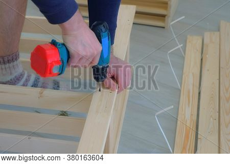 Man Screwing Boards With Screws Using Electric Screwdriver Collecting Rack Furniture Bookcase, Hands