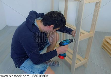 Young Man Screwing Boards With Screws Using Electric Screwdriver Collecting Rack Furniture Bookcase.