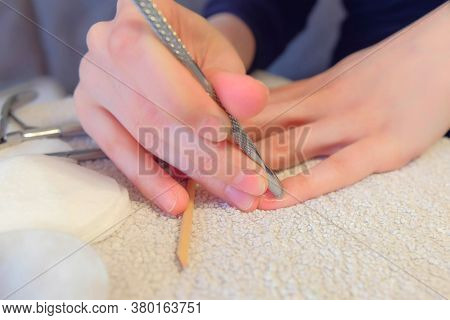 Woman Removes Pushing Cuticle With Pusher On Her Nail Making Manicure Herself At Home, Hands Closeup