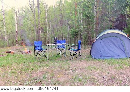Camp Tent, Chairs, Table And Campfire In Forest Camping, Nature Trip At Summer. Campsite On Glade In