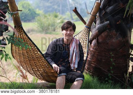 Agriculturist Male With Loincloth Across The Shoulder Sit Relaxing In The Basketry Crib On The Natur