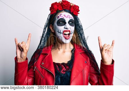 Woman wearing day of the dead costume doing rock and roll gesture with fingers angry and mad screaming frustrated and furious, shouting with anger. rage and aggressive concept.