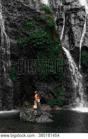 A Beautiful Girl Embraces A Man Of Athletic Build At The Waterfall. Honeymoon Trip. A Couple In Love