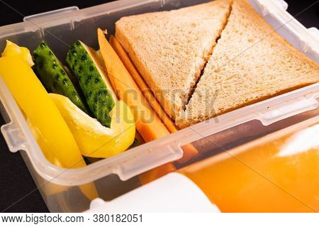 Bread Sandwich And Vegetables In A Lunch Box Next To A Bottle Of Juice. Healthy Lunch, Plant Based O