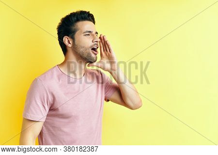 Young Handsome Man Shouting And Screaming Loud To Side With Hand On Mouth And Copy Space For Text .