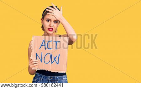 Young beautiful blonde woman holding act now banner stressed and frustrated with hand on head, surprised and angry face