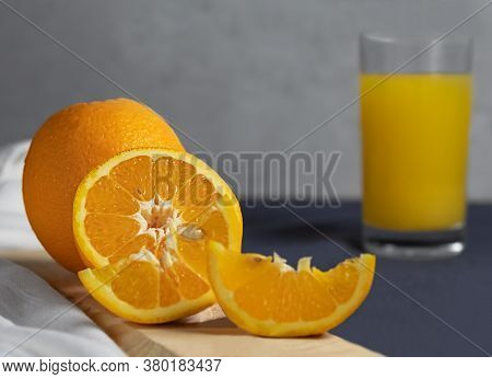 In The Foreground, A Half Of An Orange, Slimes, An Orange On A Wooden Stand On A Gray Background. Or