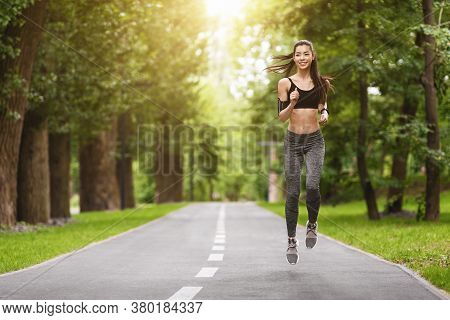 Morning Run. Sporty Korean Girl Jogging Outdoors In City Park, Feeling Healthy And Motivated, Runnin