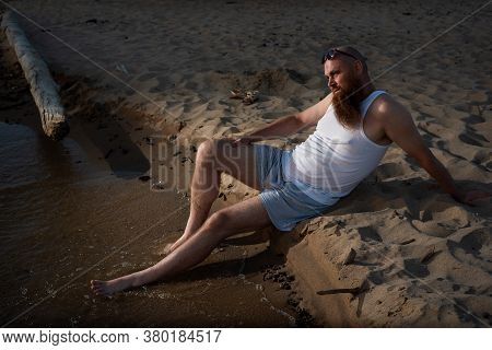 Funny Bald Man With Red Beard Posing On The Beach At Sunset. A Humorous Male Parody Of A Glamorous G