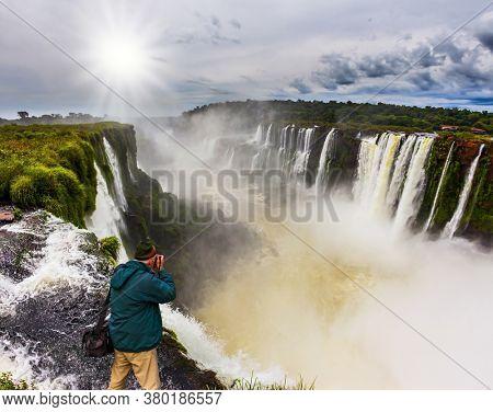 Parana River. Devil's Throat /Garganta del Diablo/ is the most grandiose part of the Iguazu Falls. The autumn sun shines through the clouds. Concept of active and extreme tourism