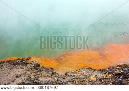 Orange shores of a hot lake with gas bubbles. Thermal Wonderland Champagne. Wai-O-Tapu, New Zealand. The geothermal zone of Rotorua. The concept of exotic, ecological and photo tourism