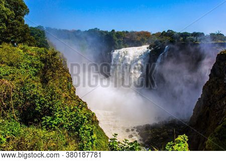 Giant cloud of mist rose above the waterfall Victoria Falls. Journey after the wet season. The waterfall is located on the Zambezi River. Concept of extreme and photo tourism