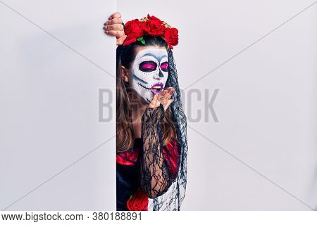 Young woman wearing day of the dead custome holding blank empty banner bored yawning tired covering mouth with hand. restless and sleepiness.