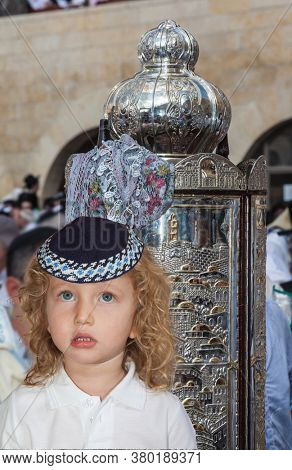 The Jews brought the Torah Scroll for prayer. Western Wall of the Temple. Autumn Jewish holiday Sukkot. Handsome little boy with blond side curls and blue eyes, in skullcap