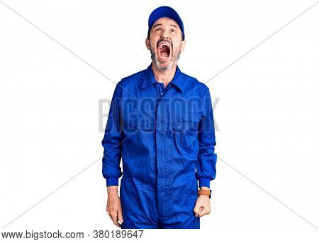 Middle age handsome man wearing mechanic uniform angry and mad screaming frustrated and furious, shouting with anger. rage and aggressive concept.