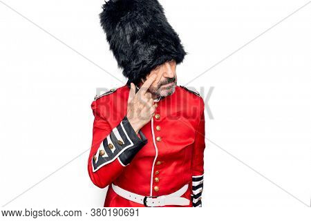 Middle age handsome wales guard man wearing traditional uniform over white background Pointing to the eye watching you gesture, suspicious expression
