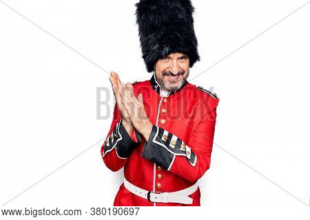Middle age handsome wales guard man wearing traditional uniform over white background clapping and applauding happy and joyful, smiling proud hands together