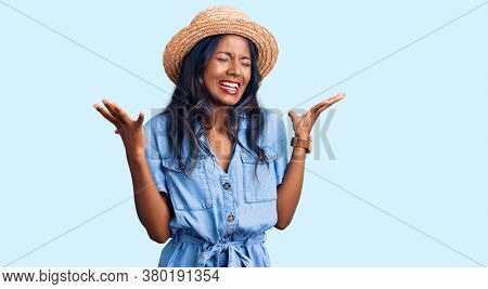 Young indian girl wearing summer hat celebrating mad and crazy for success with arms raised and closed eyes screaming excited. winner concept