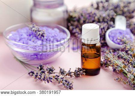 Lavender Essential Oil Glass Bottle Dropper With Bath Product Violet Sea Salt On Pink Color Backgrou