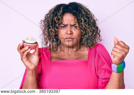 Young african american plus size woman holding cupcake annoyed and frustrated shouting with anger, yelling crazy with anger and hand raised