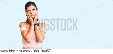 Young beautiful woman wearing casual clothes tired hands covering face, depression and sadness, upset and irritated for problem