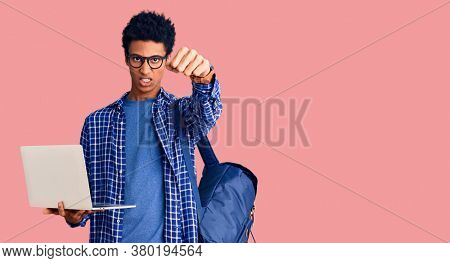 Young african american man holding student backpack using laptop annoyed and frustrated shouting with anger, yelling crazy with anger and hand raised