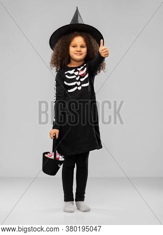 halloween, holiday and childhood concept - smiling african american girl in black costume dress and witch hat with candies trick-or-treating and showing thumbs up gesture over grey background