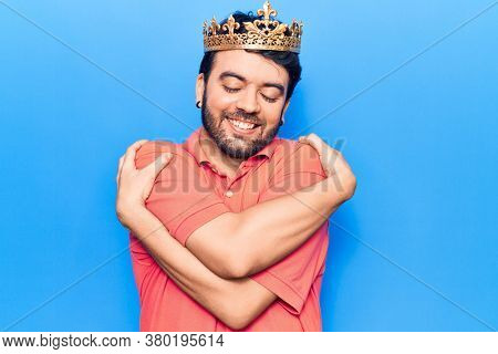 Young hispanic man wearing king crown hugging oneself happy and positive, smiling confident. self love and self care