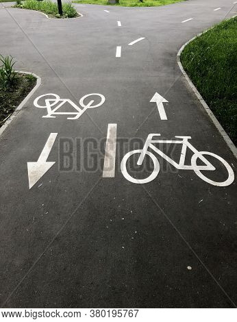 Bike Lane. The Bike Signs On The Asphalt Are Painted With White Paint. Two Bike Path Signs Pointing