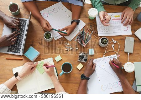 Top View Close Up Of Multi-ethnic Group Of People Working Together At Cluttered Wooden Table With Co