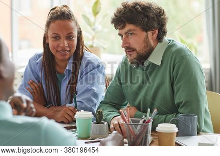 Portrait Of Creative Bearded Man Brainstorming Ideas While Working On Team Project With Multi-ethnic