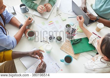 High Angle View At Contemporary Creative Team Working Together At Cluttered Table With Coffee Mugs A