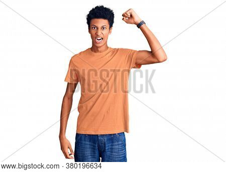 Young african american man wearing casual clothes angry and mad raising fist frustrated and furious while shouting with anger. rage and aggressive concept.
