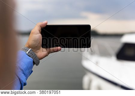 Man Photographing Yacht With Smartphone At The River