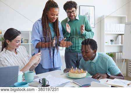 Multi-ethnic Group Of People Celebrating Birthday In Office, Focus On Young African-american Man Blo