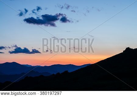 Warm Gradient Of Dawn Sky Above Layers Of Mountain And Rock Silhouettes. Vivid Alpine Landscape With