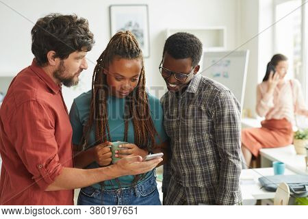 Waist Up Portrait Of Multi-ethnic Group Of People Looking At Smartphone Screen While Standing In Off