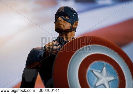 AUGUST 7 2020: Portrait of Marvel comic superhero Captain America of the Avengers with USA flag - Hasbro action figure