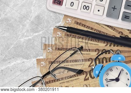 2000 Hungarian Forint Bills And Calculator With Glasses And Pen. Business Loan Or Tax Payment Season