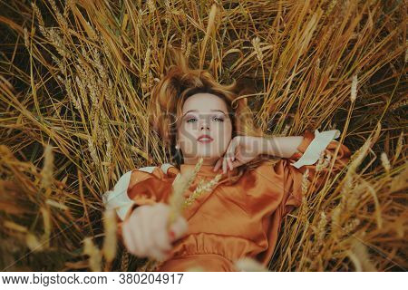 An Elegant Model Lies On A Wheat Field Enjoys Nature. The Concept Of Natural Products, Unity With Na