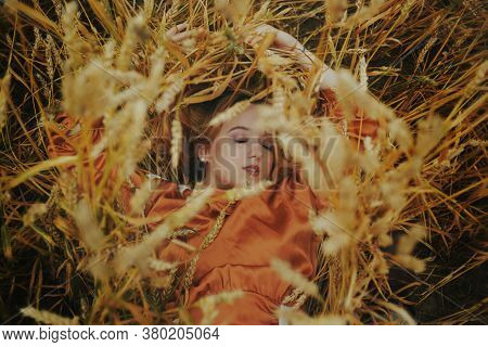 A Girl In A Golden Wheat Field Lies In A Dress. A Woman Is Sleeping In Nature, The Model Has Closed