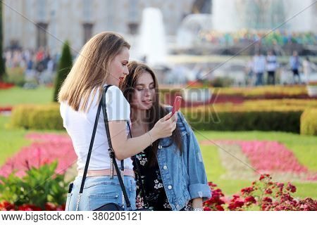 Moscow, Russia - August 2020: Two Girls Standing In Summer Park And Looking On Smartphone Screen. Co