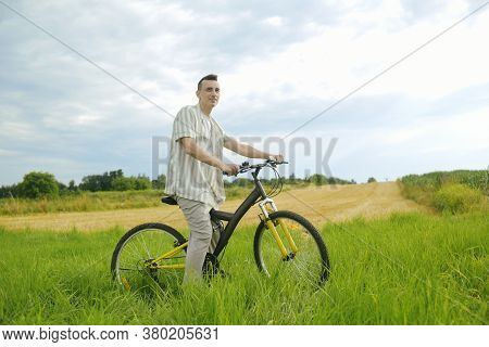 A Man On A Mountain Bike. A Fashionable Guy Came To Nature In The Field.
