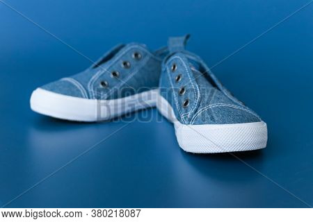 Blue Children's Sneakers With White Soles Without Laces On A Blue Background
