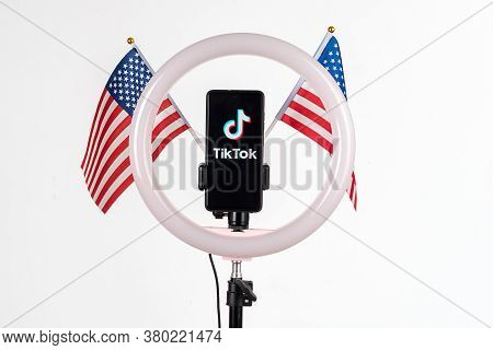 Tiktok Logo On A Smartphone Attached To A Round Lamp With A Tripod And Two American Flags On A White