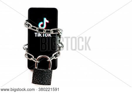 Tiktok Logo On A Smartphone. The Telephone Is Tied With An Iron Chain And Has A Large Padlock On It.